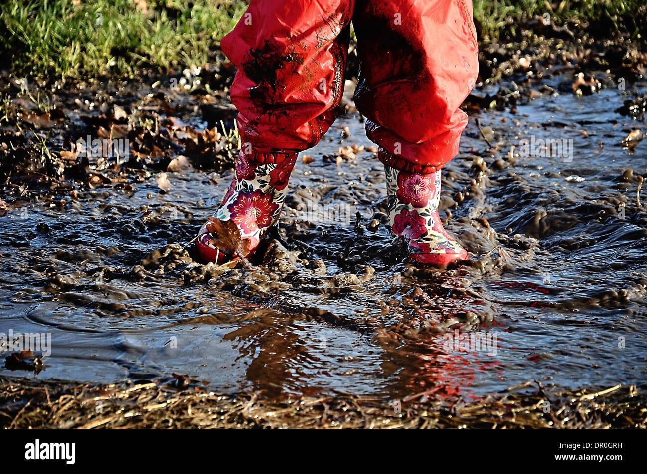 Bambino in stivali da pioggia spruzzi in una pozza Immagini Stock