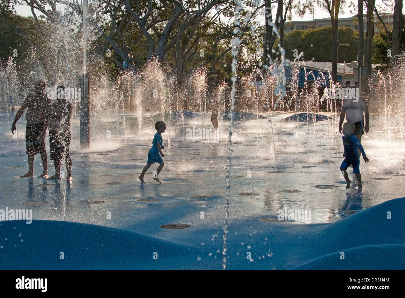 Adulti E Bambini Che Giocano In Acqua Che Sgorga Dalla Schiera Di