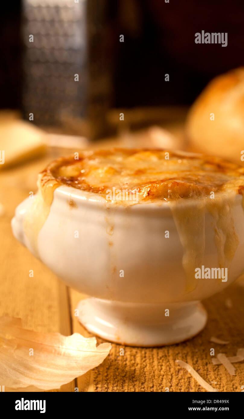 Zuppa di cipolle alla francese con formaggio grattugiato e una pagnotta di pane Immagini Stock
