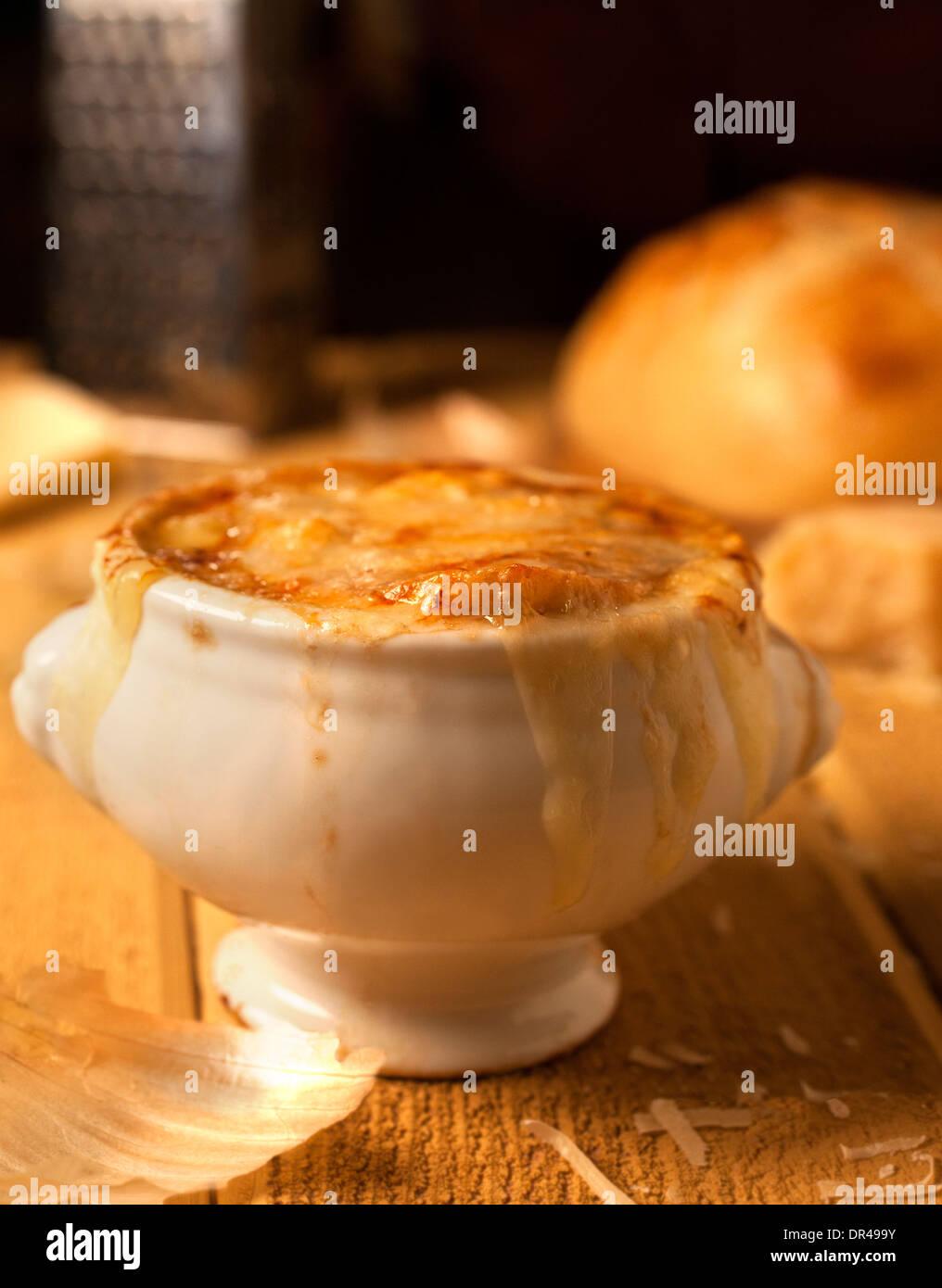 Zuppa di cipolle alla francese con formaggio grattugiato e una pagnotta di pane francese Immagini Stock