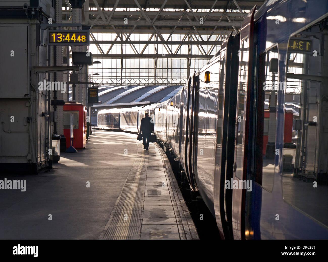 Concetto di ridondanza / sconsolato solo l uomo che porta due valigette di scrivania contenuto camminando sulla banchina della stazione di treno carrello a 13.44 pm Immagini Stock