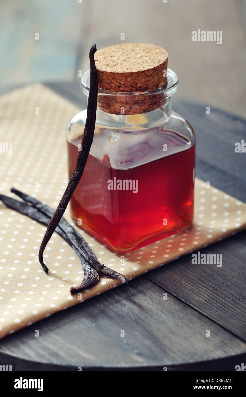 Bottiglia con essenza di vaniglia su ackground in legno Immagini Stock
