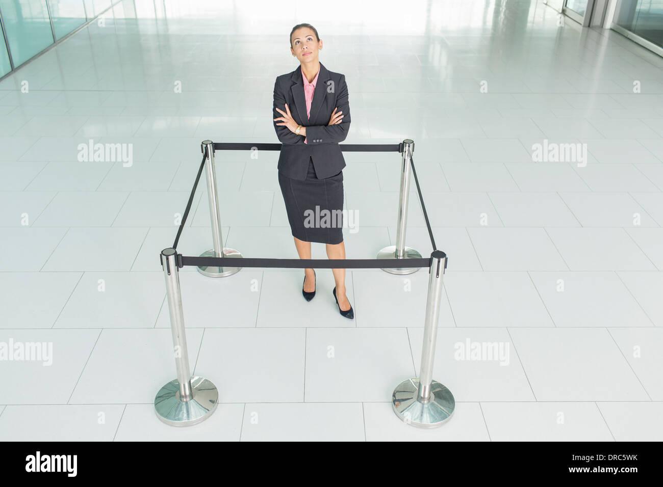 Imprenditrice in piedi in una cordata-off square Immagini Stock
