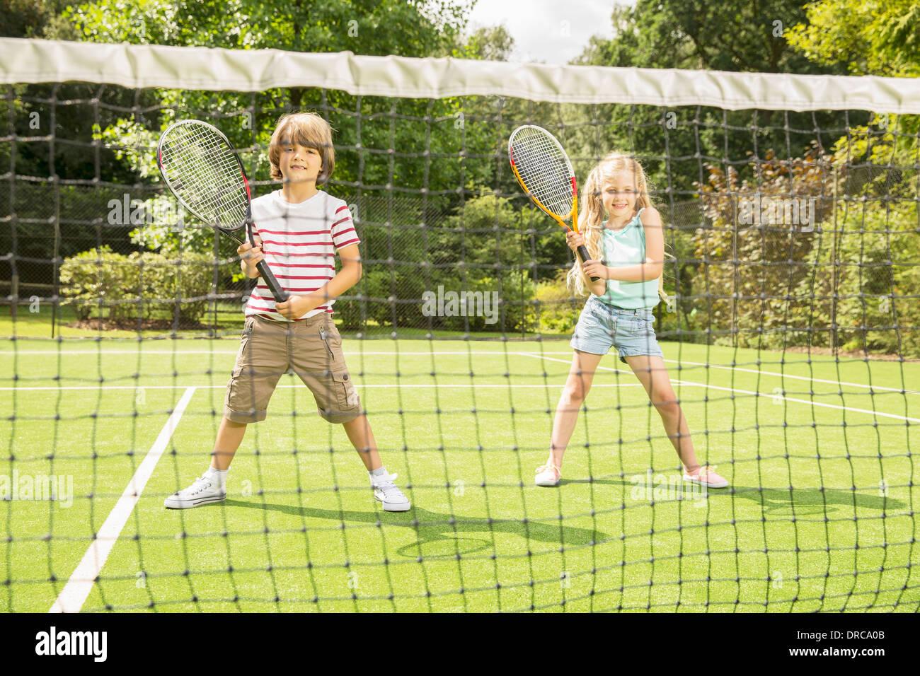 I bambini giocando a tennis su erba corte Immagini Stock