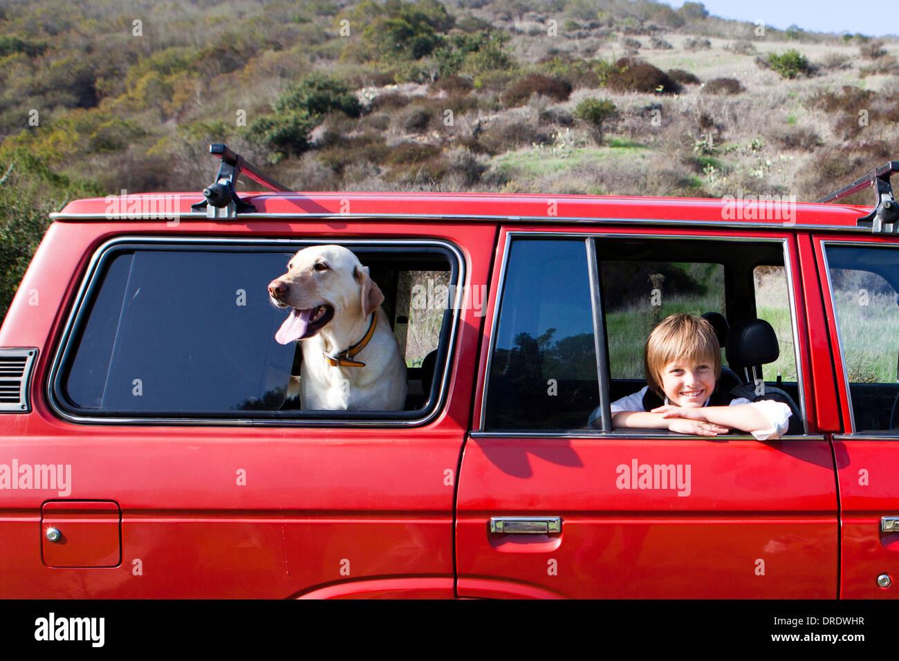 Ragazzo e cane appendere fuori dalle finestre di un suv rosso Immagini Stock