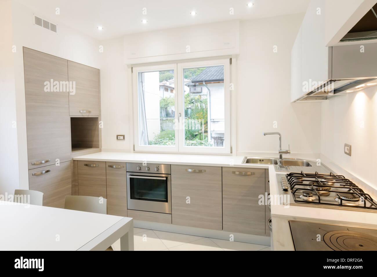 Cucina moderna con interni armadi in legno e il bianco da tavola Immagini Stock