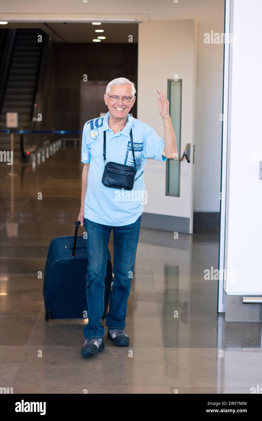Felice anziani uomo turistica sventolare un saluto nella sala degli arrivi dell'aeroporto. Immagini Stock