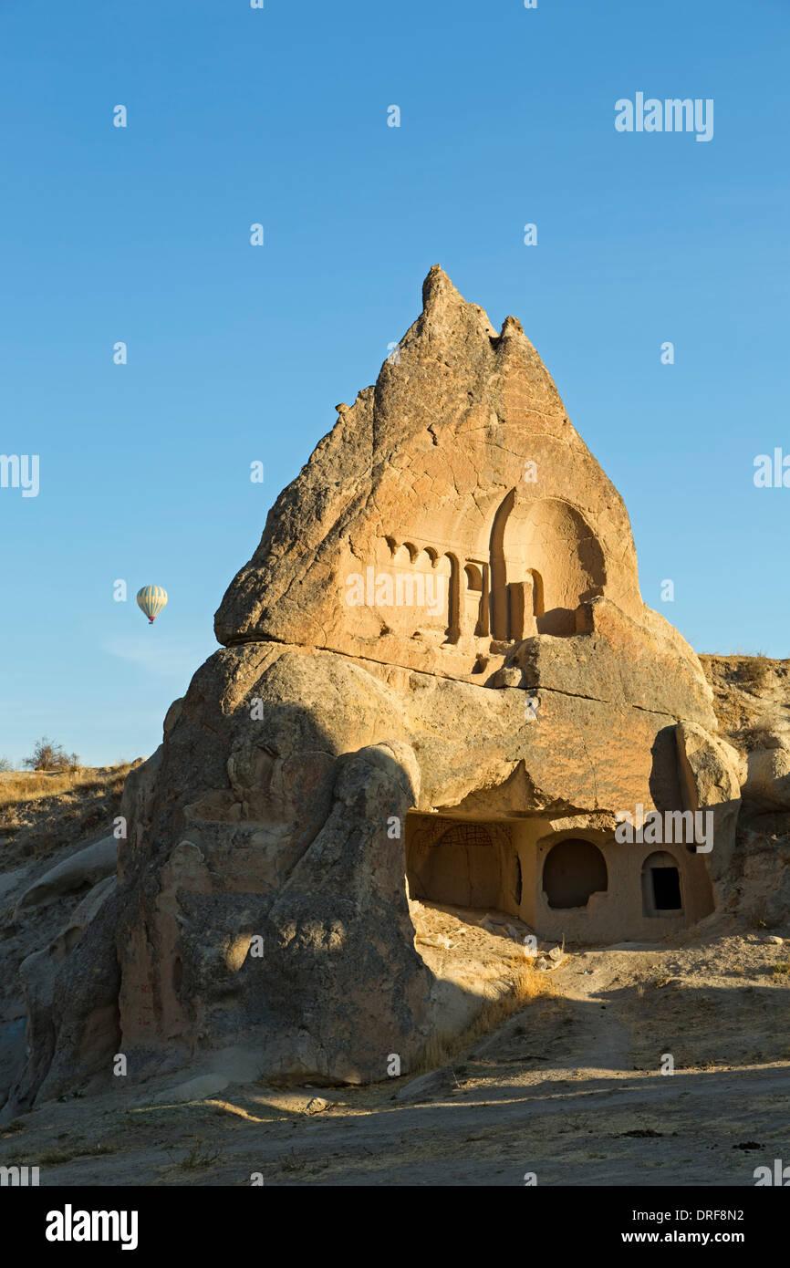 Abitazione in fairy camino e una mongolfiera, spade Valley (Meskendir), vicino a Goreme, Cappadocia, Turchia Foto Stock