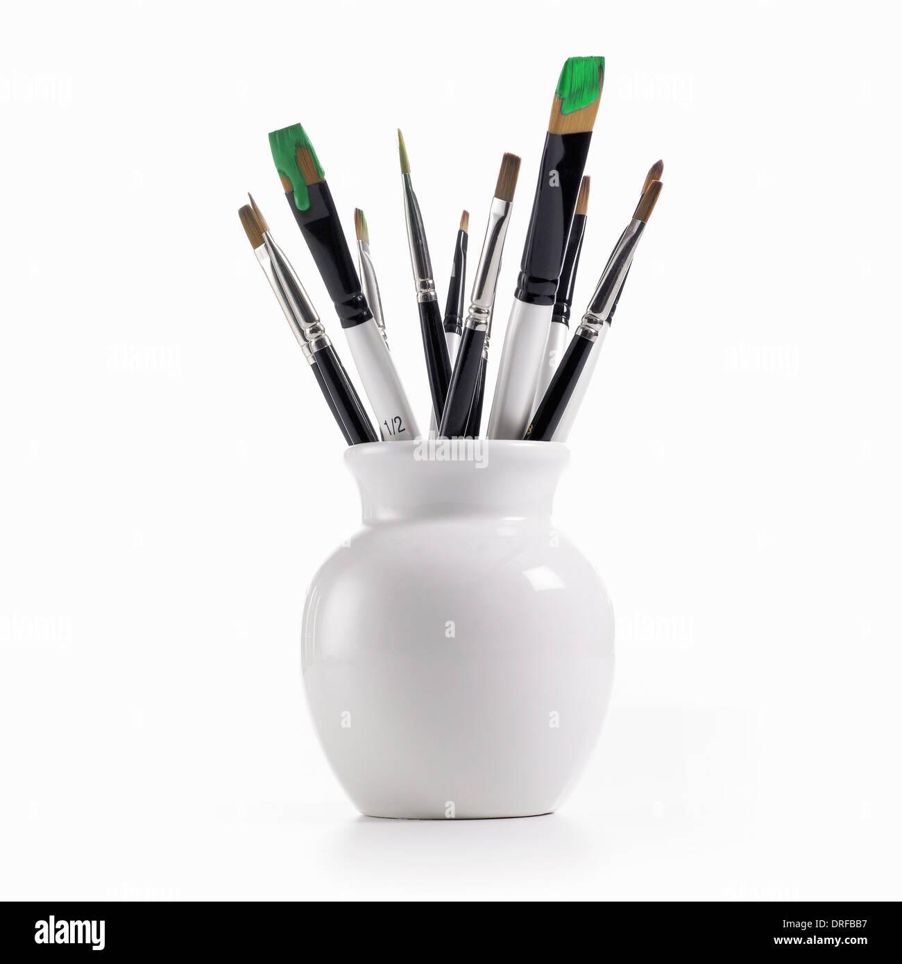 Porcellana Bianca pot pennelli caricato della vernice verde Immagini Stock