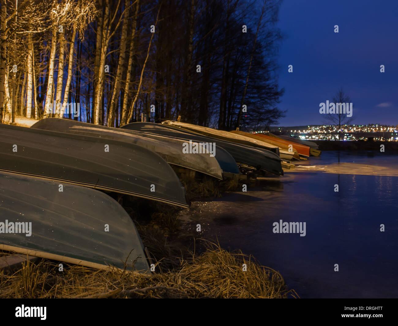 Barche a remi sollevata da un lago ghiacciato Immagini Stock