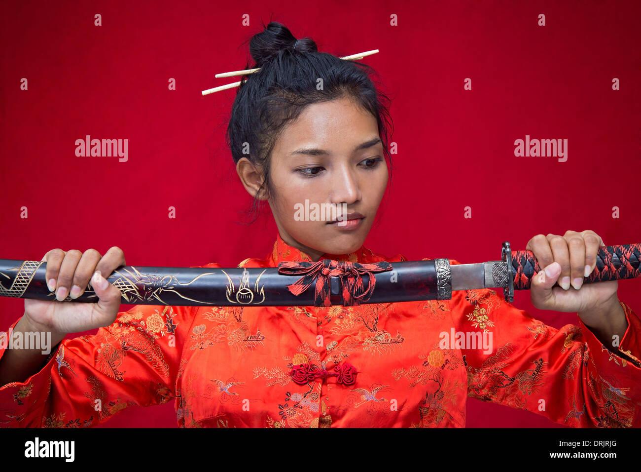 Donna asiatica che tiene una spada Foto Stock