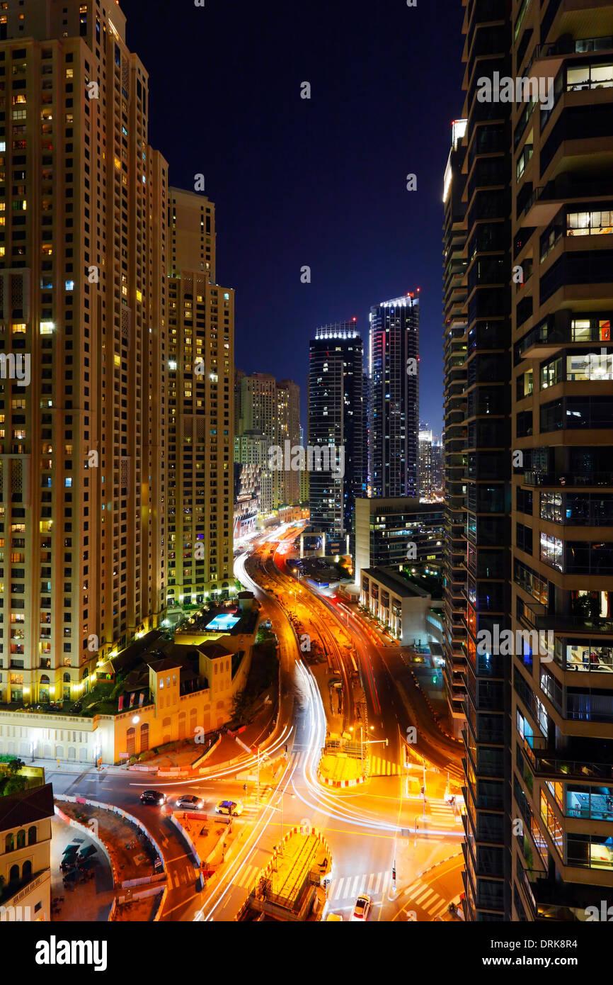 Edifici e street in Dubai Marina di notte. Re Salman bin Abdulaziz Al Saud st. Immagini Stock