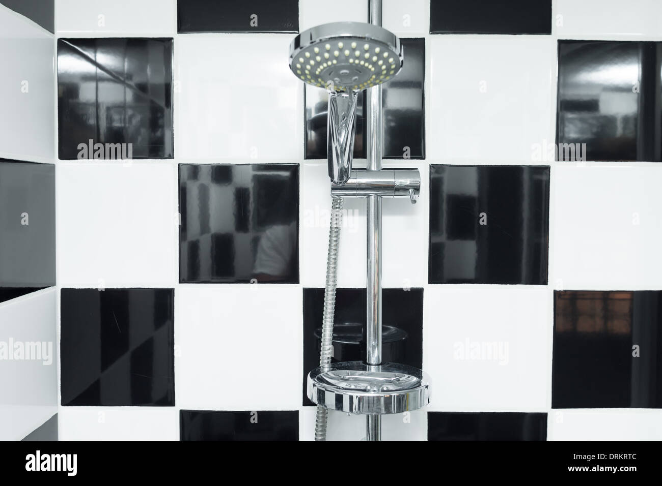 Doccia moderna testa in un bagno a scacchi con piastrelle bianche