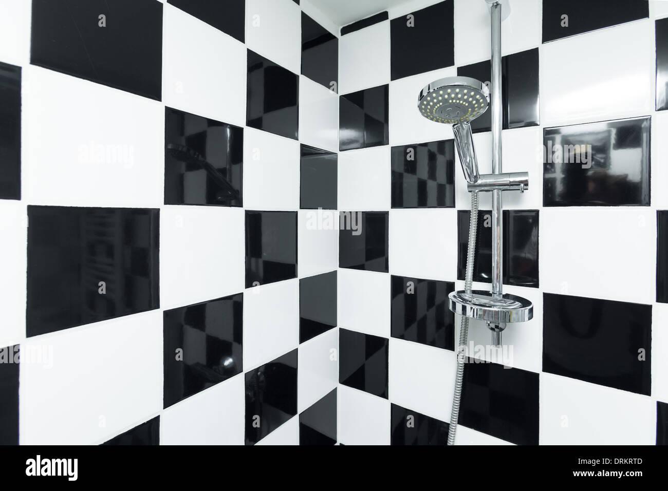 Doccia moderna in un bagno a scacchi con piastrelle bianche e nere