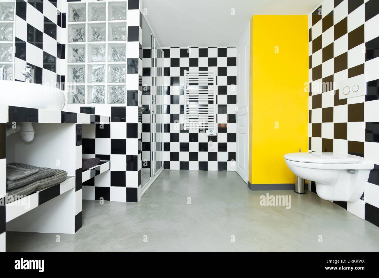 Bagno moderno con a scacchi in piastrelle bianche e nere sulle