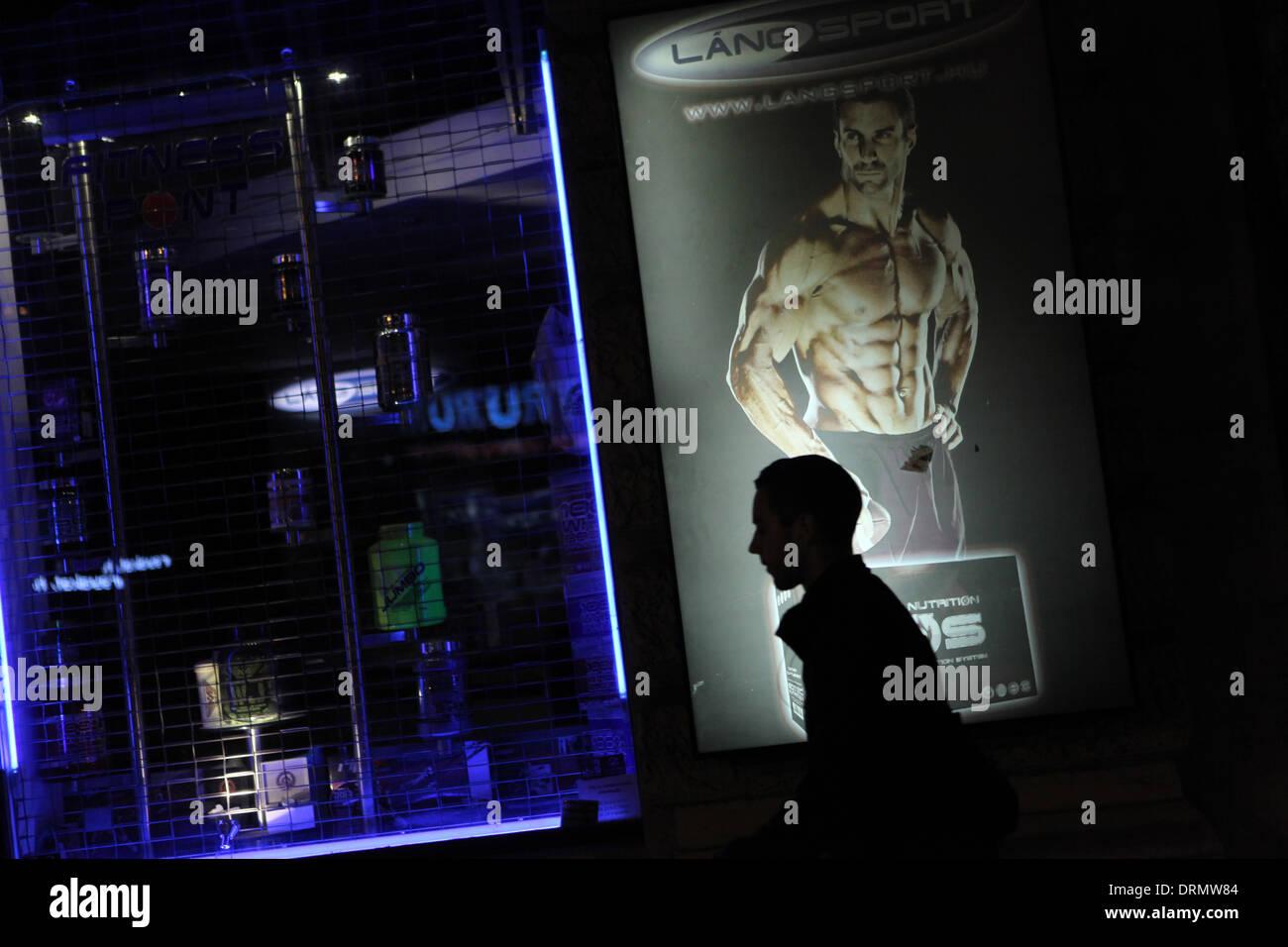 Un uomo passa alla vetrina di un negozio decorata con pubblicità di bodybuilding supplemento in Budapest, Ungheria. Immagini Stock