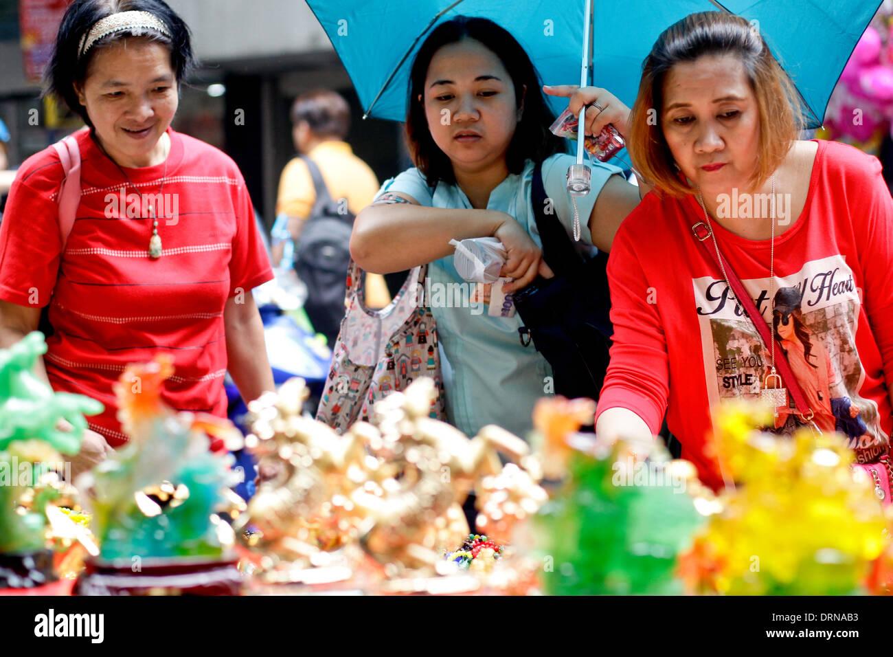 Manila, Filippine. Il 30 gennaio 2014. Una donna negozi per portafortuna in Chinatown Manila il 30 gennaio 2014 un giorno prima del nuovo anno cinese, l'anno del cavallo. Foto di Mark Cristino/Alamy Live News Immagini Stock