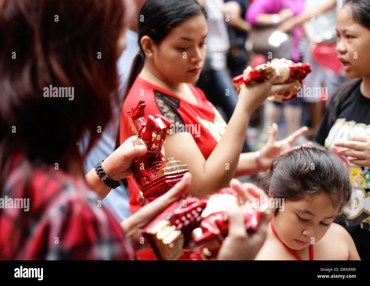 Manila, Filippine. Il 30 gennaio 2014. Shoppers guardare portafortuna in forma di cavalli in Chinatown Manila il 30 gennaio 2014 un giorno prima del nuovo anno cinese, l'anno del cavallo. Foto di Mark Cristino/Alamy Live News Immagini Stock