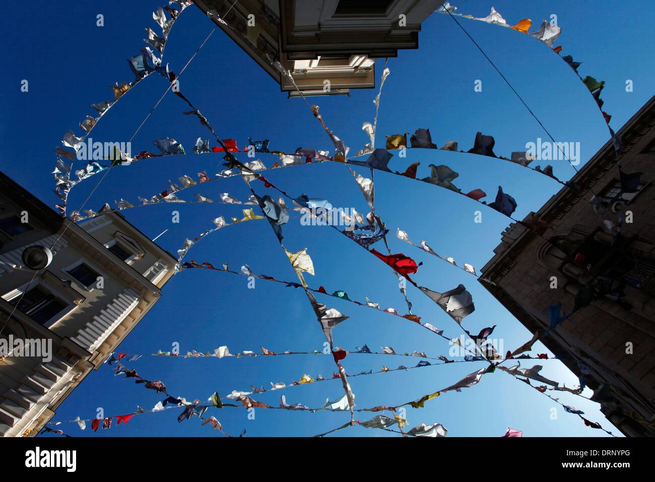Le linee di abbigliamento appeso tra gli edifici con cielo blu sullo sfondo Immagini Stock