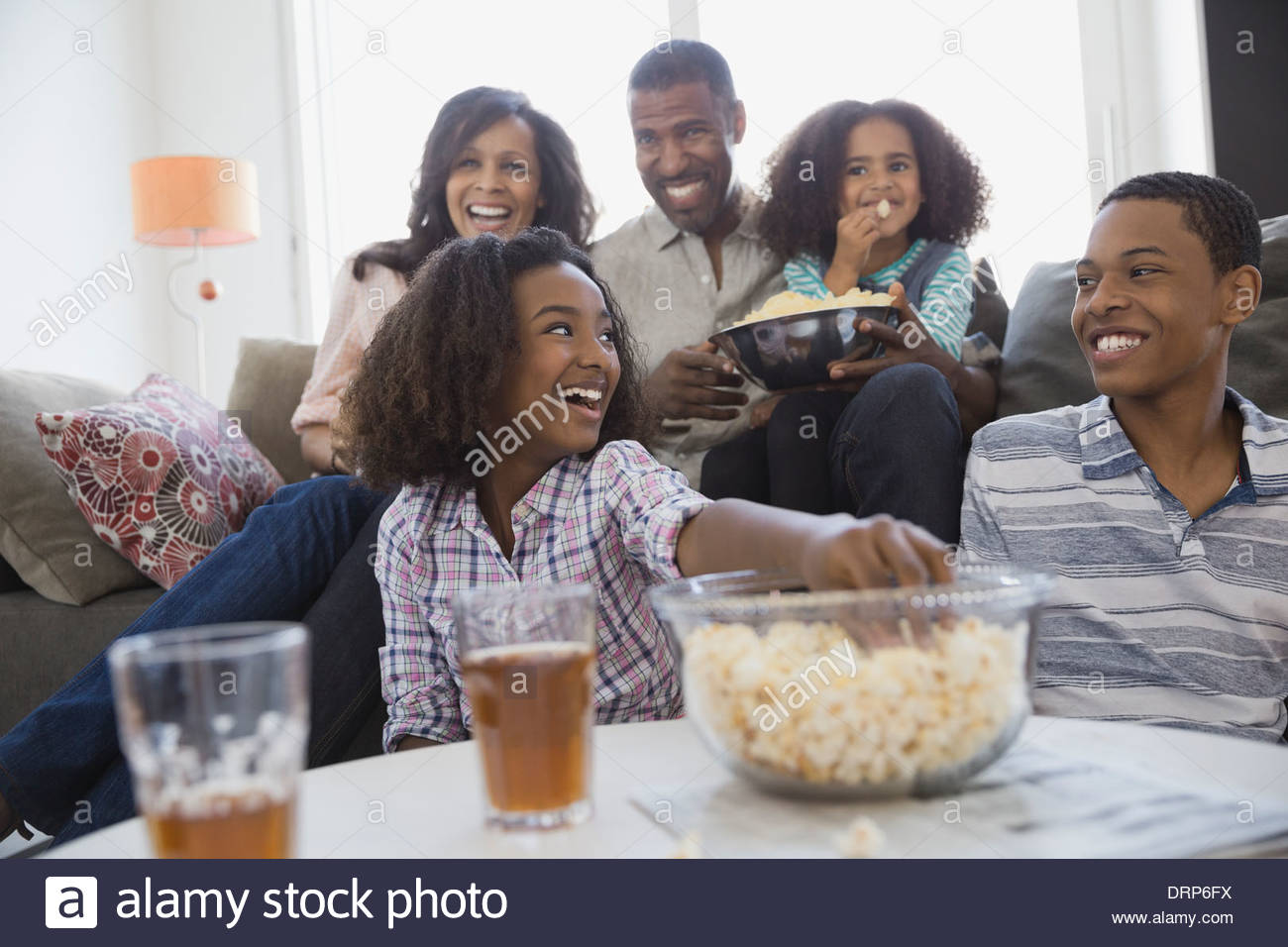 Famiglia di guardare la televisione insieme a casa Immagini Stock