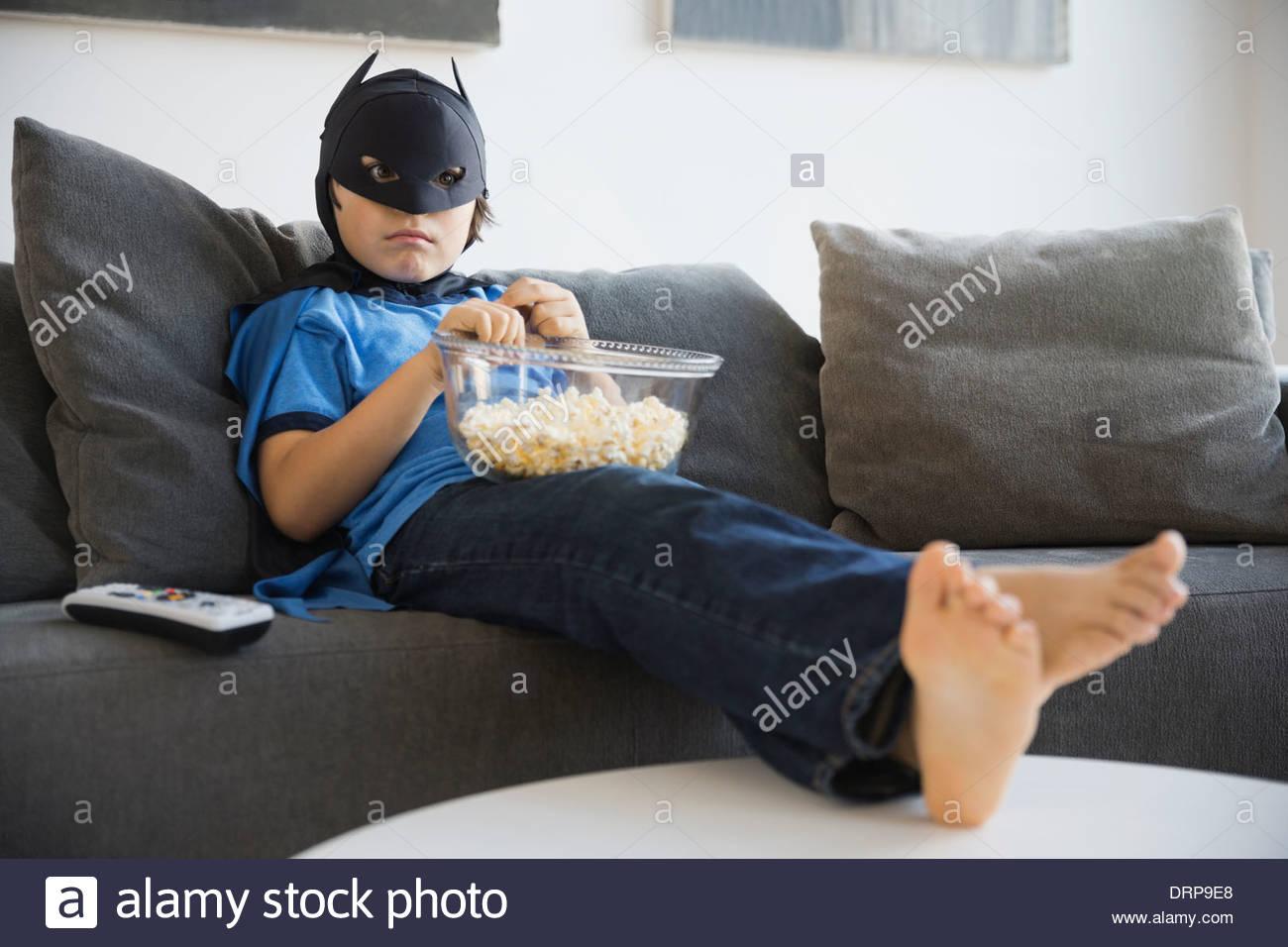 Ragazzo vestito in costume da supereroe guardando la TV a casa Immagini Stock