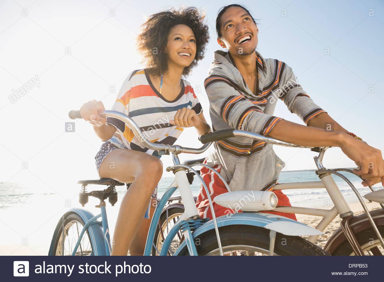 Giovane con le biciclette sulla spiaggia Immagini Stock