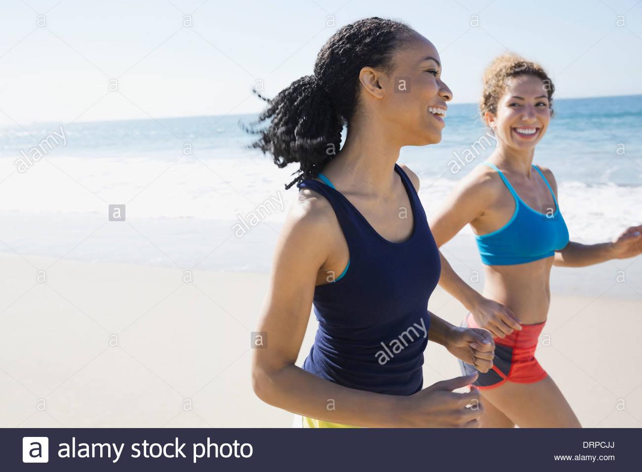 Amici di sesso femminile jogging sulla spiaggia Immagini Stock