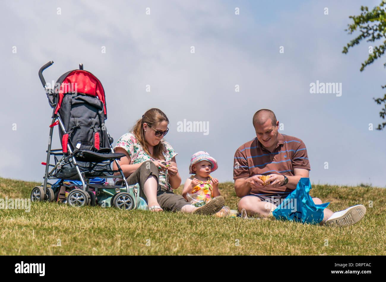 Una coppia e il loro bambino avente un picnic su Box Hill, Surrey, Inghilterra Immagini Stock