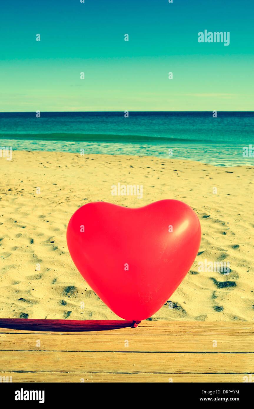 Un cuore rosso a forma di palloncino su una spiaggia, con un effetto retrò Immagini Stock