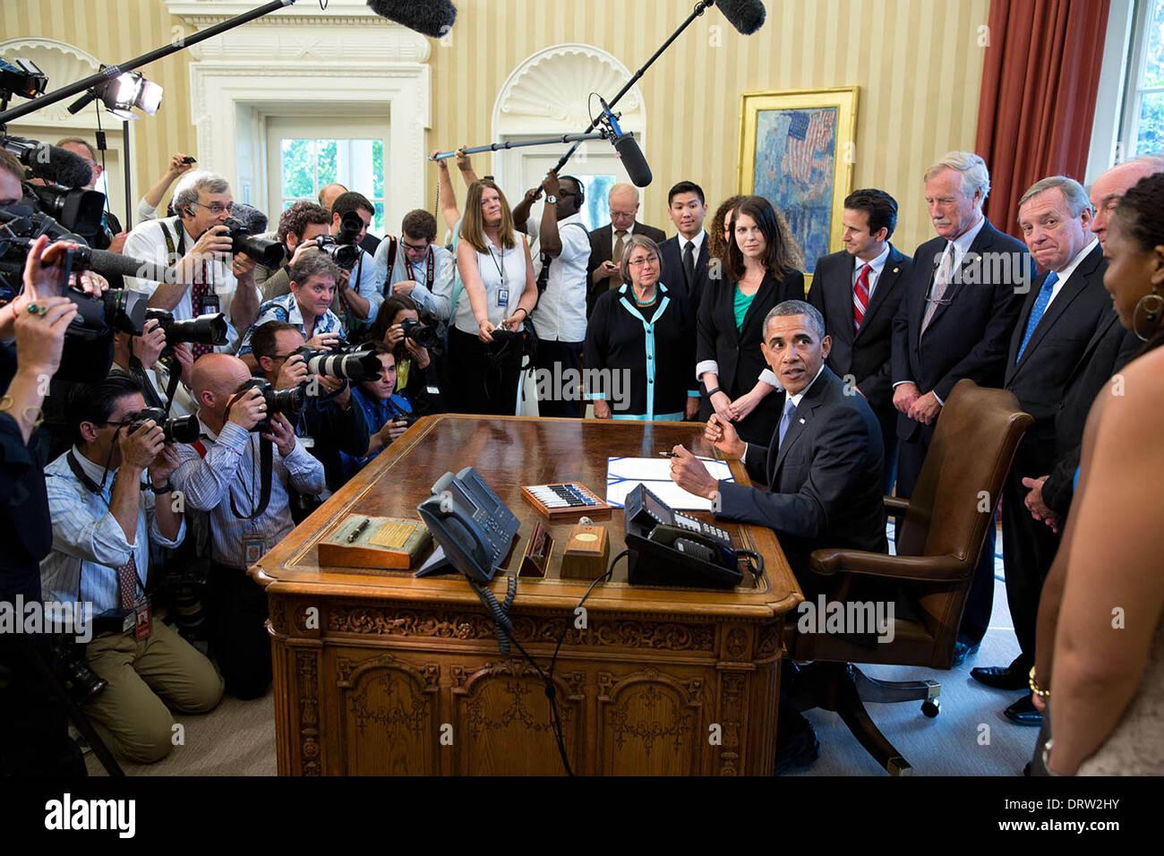 Il Presidente Usa Barack Obama si guarda indietro verso un gruppo di studenti prima della firma di H.R. 1911, Bipartisan Prestito studente certezza Act del 2013 nell'Ufficio Ovale della Casa Bianca il 9 agosto 2013 a Washington, DC. Immagini Stock