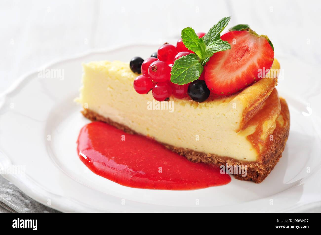 Cheesecake con frutti di bosco freschi e menta su piastra in primo piano Immagini Stock