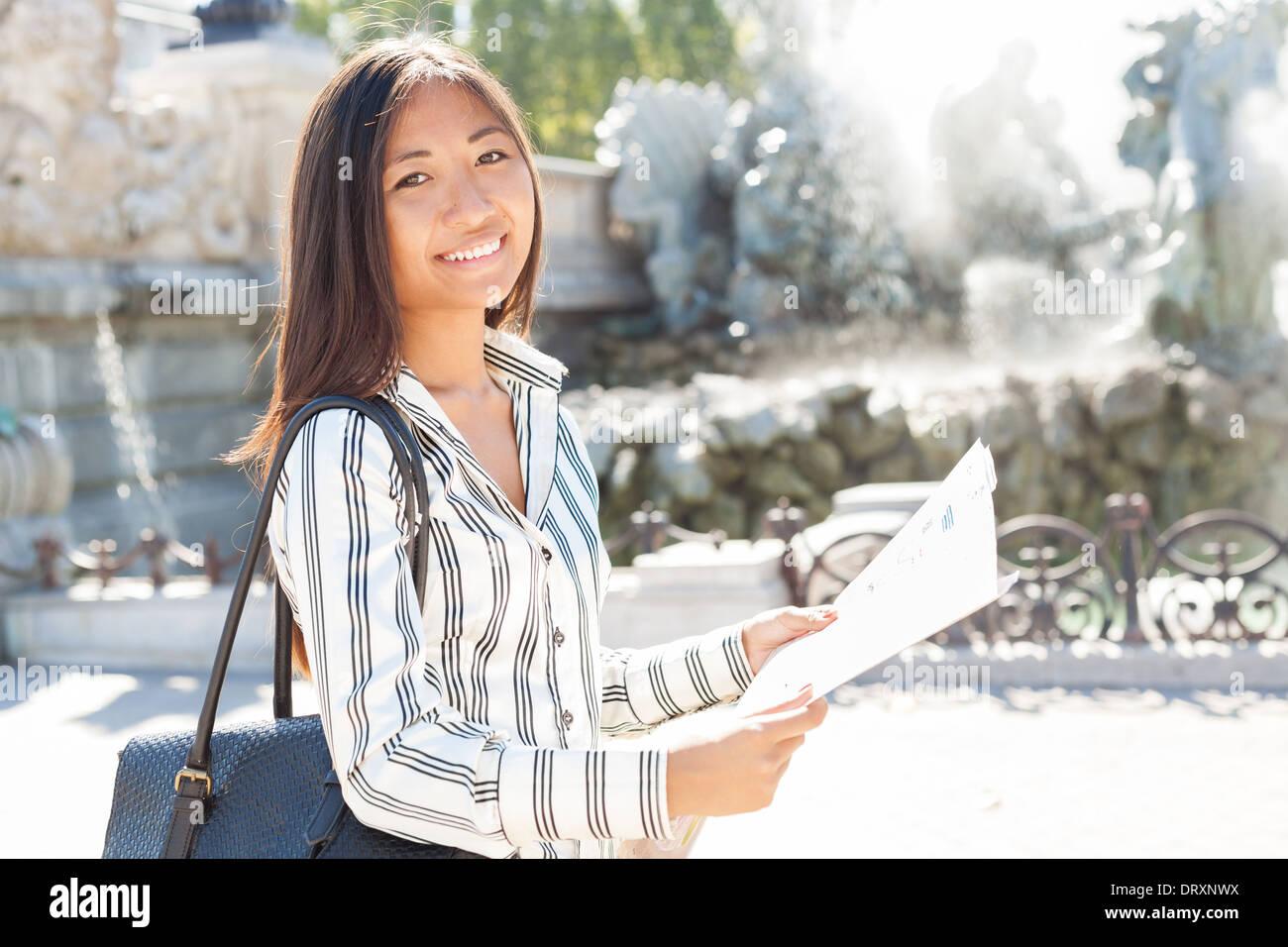 Sorridente turistici asiatici in possesso di una mappa della città Immagini Stock