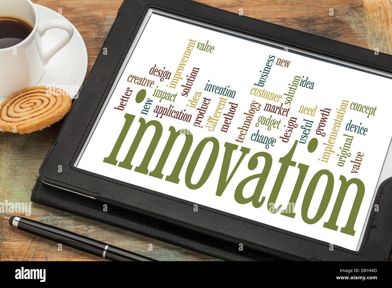 Il concetto di innovazione - word cloud su una tavoletta digitale con una tazza di caffè Immagini Stock
