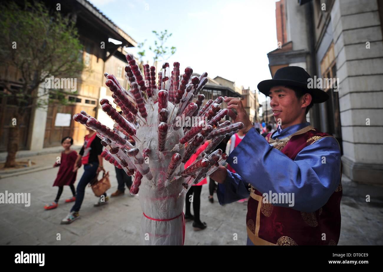 """Haikou, cinese della provincia di Hainan. 5 febbraio, 2014. Un uomo vende rivestite di zucchero haws su un bastone, un tradizionale spuntino cinese, al """"strada nello stile della Cina nel 1942' in Haikou, capitale del sud della Cina di Hainan Provincia, Febbraio 5, 2014. Come una parte di direttore Feng Antonio's movie theme park, recentemente inaugurato street imitando scene di Feng il film '1942' testimoni di un picco del turismo di recente. Credito: Guo Cheng/Xinhua/Alamy Live News Immagini Stock"""