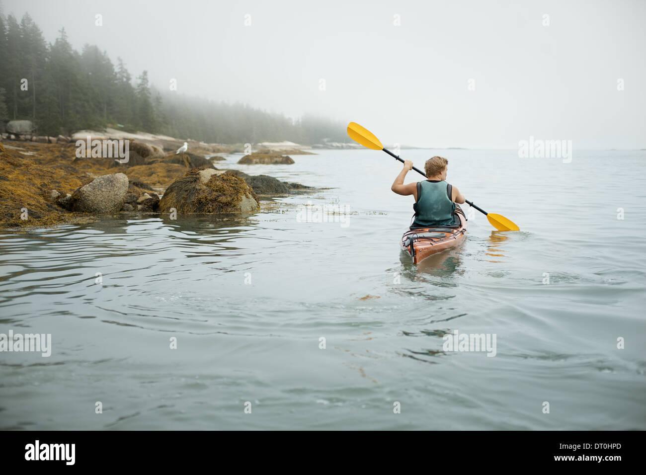 Lo stato di New York STATI UNITI D'AMERICA uomo canoa kayak su acqua calma misty condizioni Immagini Stock