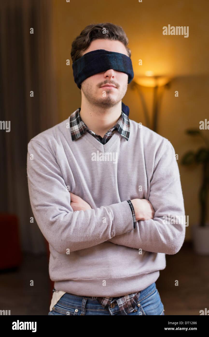 Gli occhi bendati giovane uomo di casa in soggiorno non può vedere Immagini Stock
