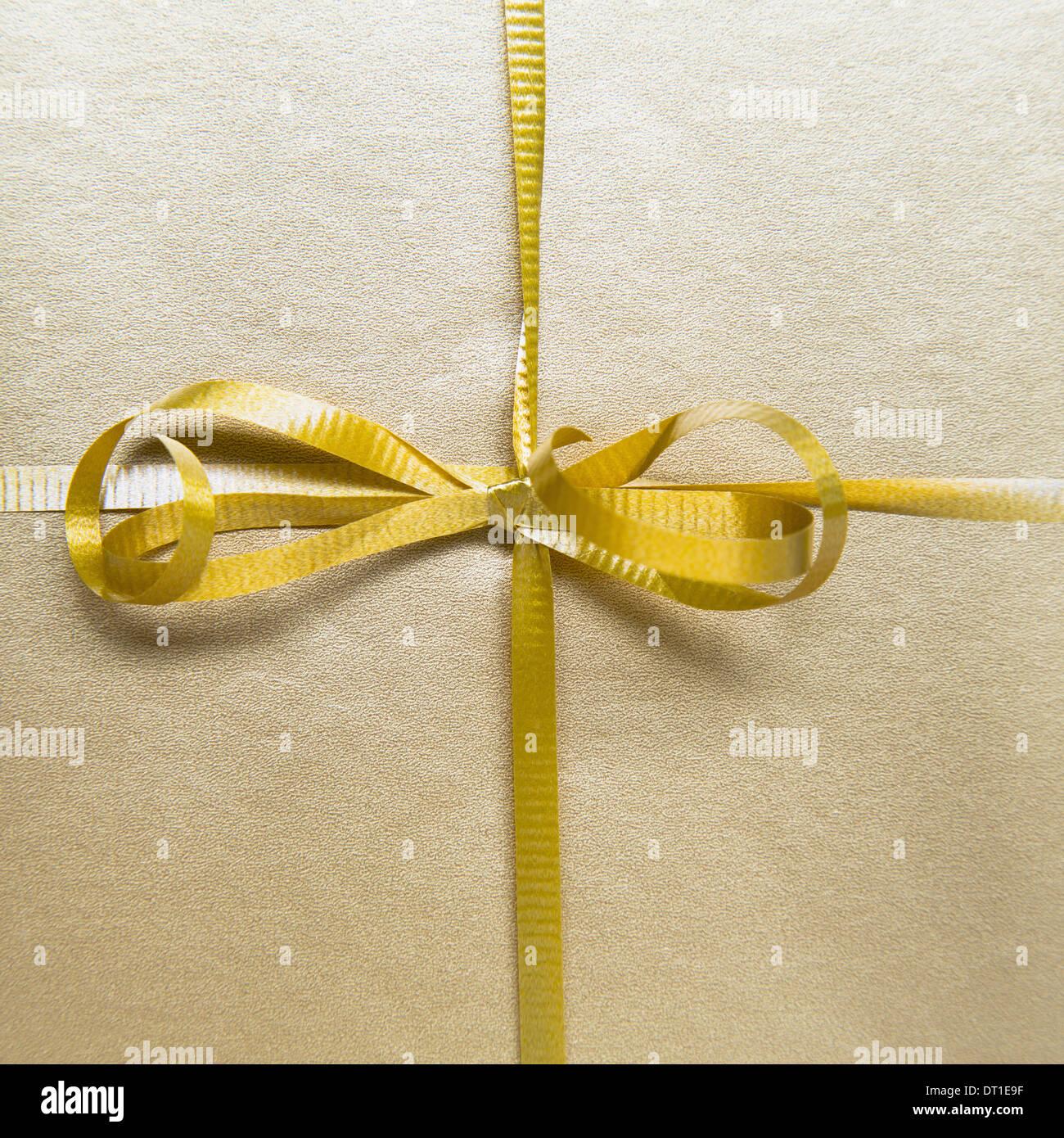 Legata a prua e nastro color oro dal dono avvolto Immagini Stock
