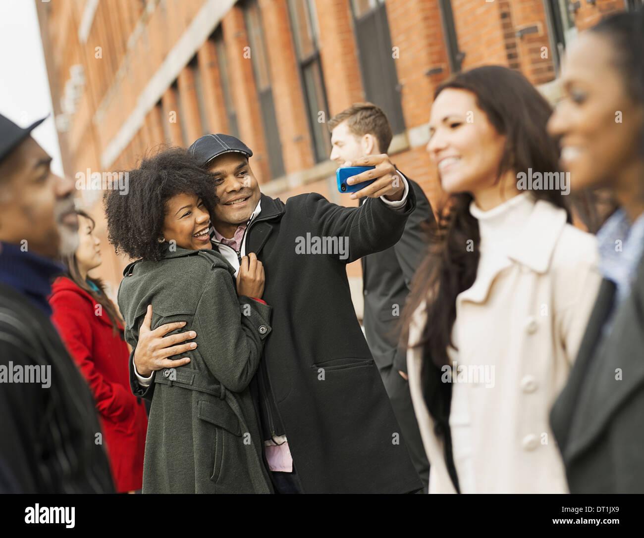 Un uomo con un telefono con fotocamera e scattare foto di gruppo baciare una giovane donna le donne e gli uomini Immagini Stock