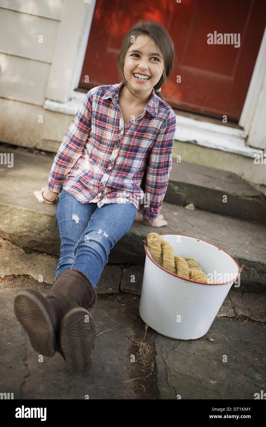 Una ragazza seduta su un gradino con un grosso secchio di ferro e guanti Immagini Stock