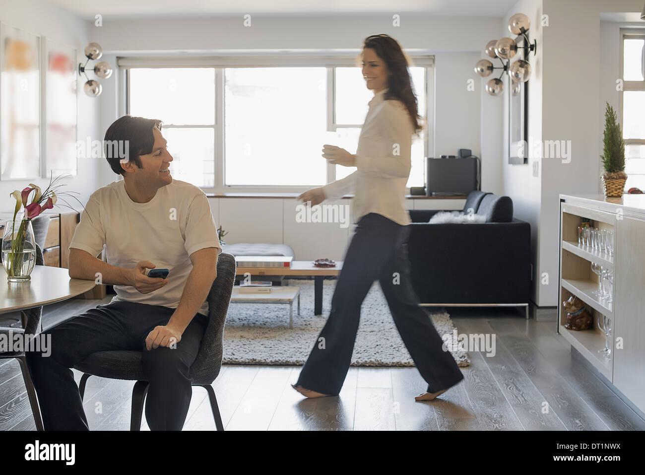 Giovane a casa uomo utilizza lo smartphone donna passato a piedi Immagini Stock