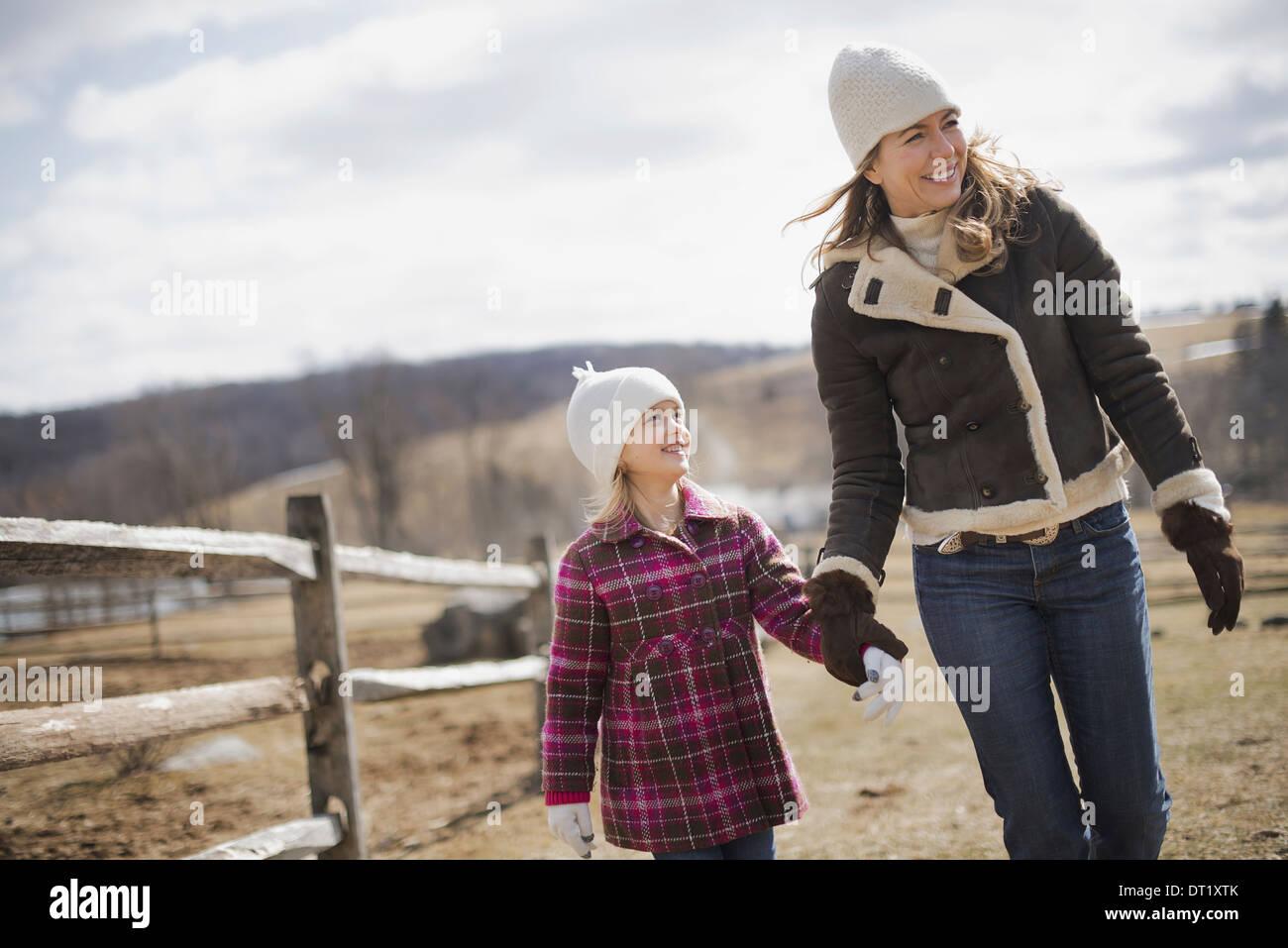 Una donna e bambino a piedi lungo un percorso mano nella mano su una fattoria in primavera meteo Immagini Stock