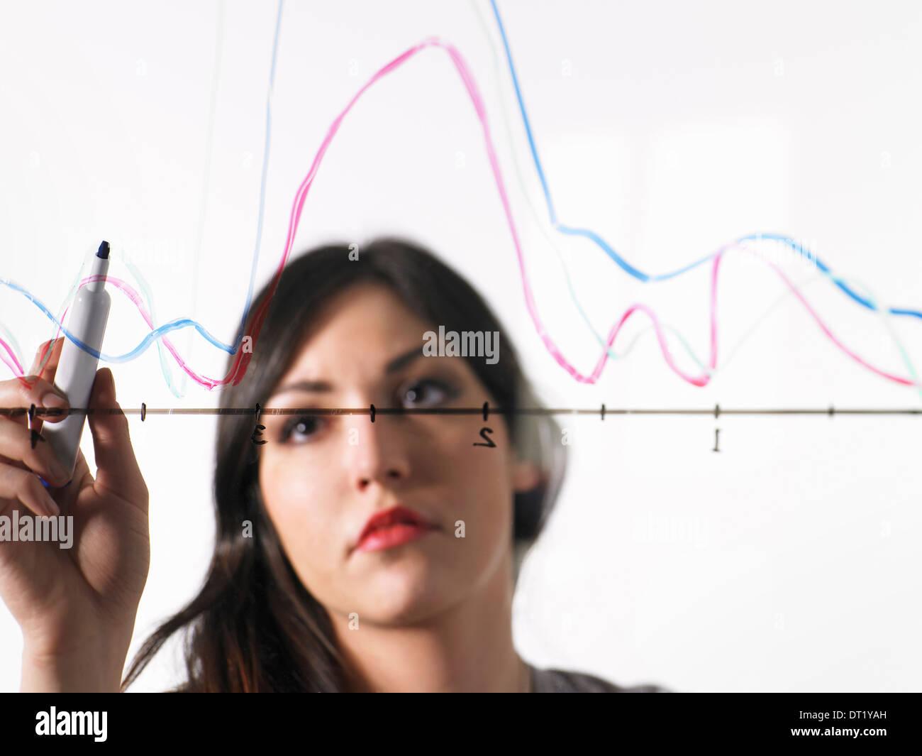 Una giovane donna di colore di disegno le linee del grafico in un grafico illustrazione su un vedere attraverso la superficie Immagini Stock