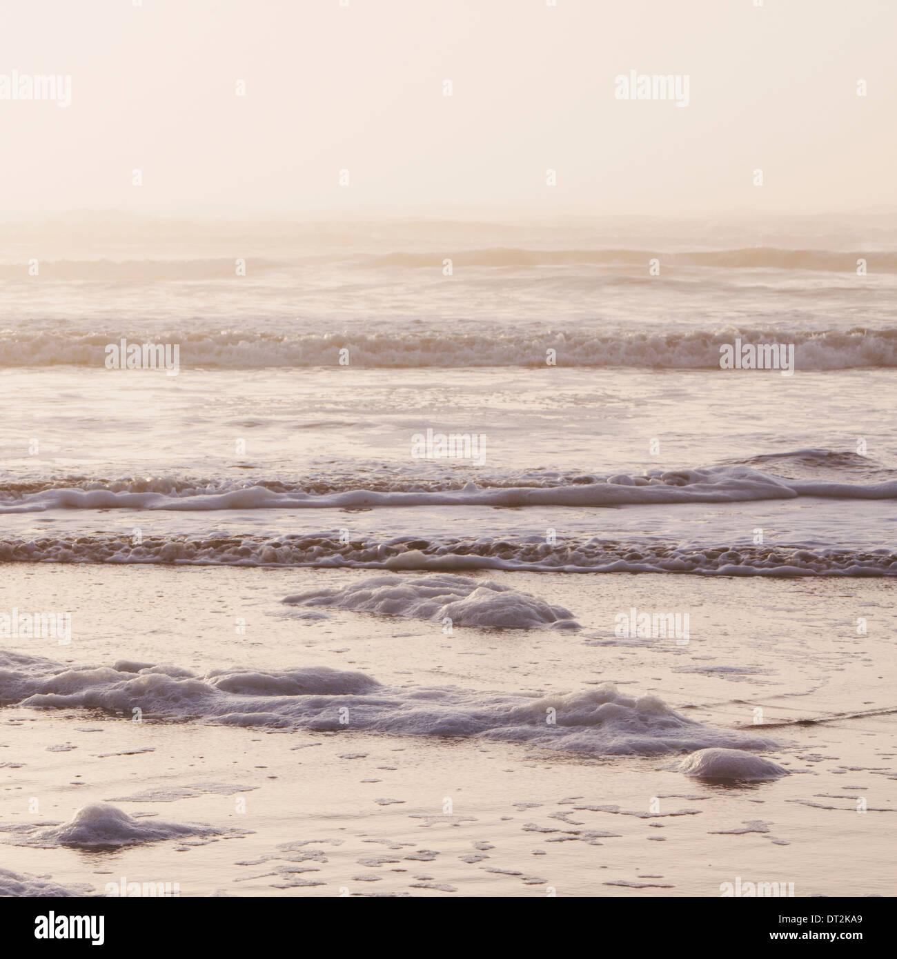 Seascape al crepuscolo di onde che si infrangono sulla riva zona di marea lungo le coste del parco nazionale di Foto Stock