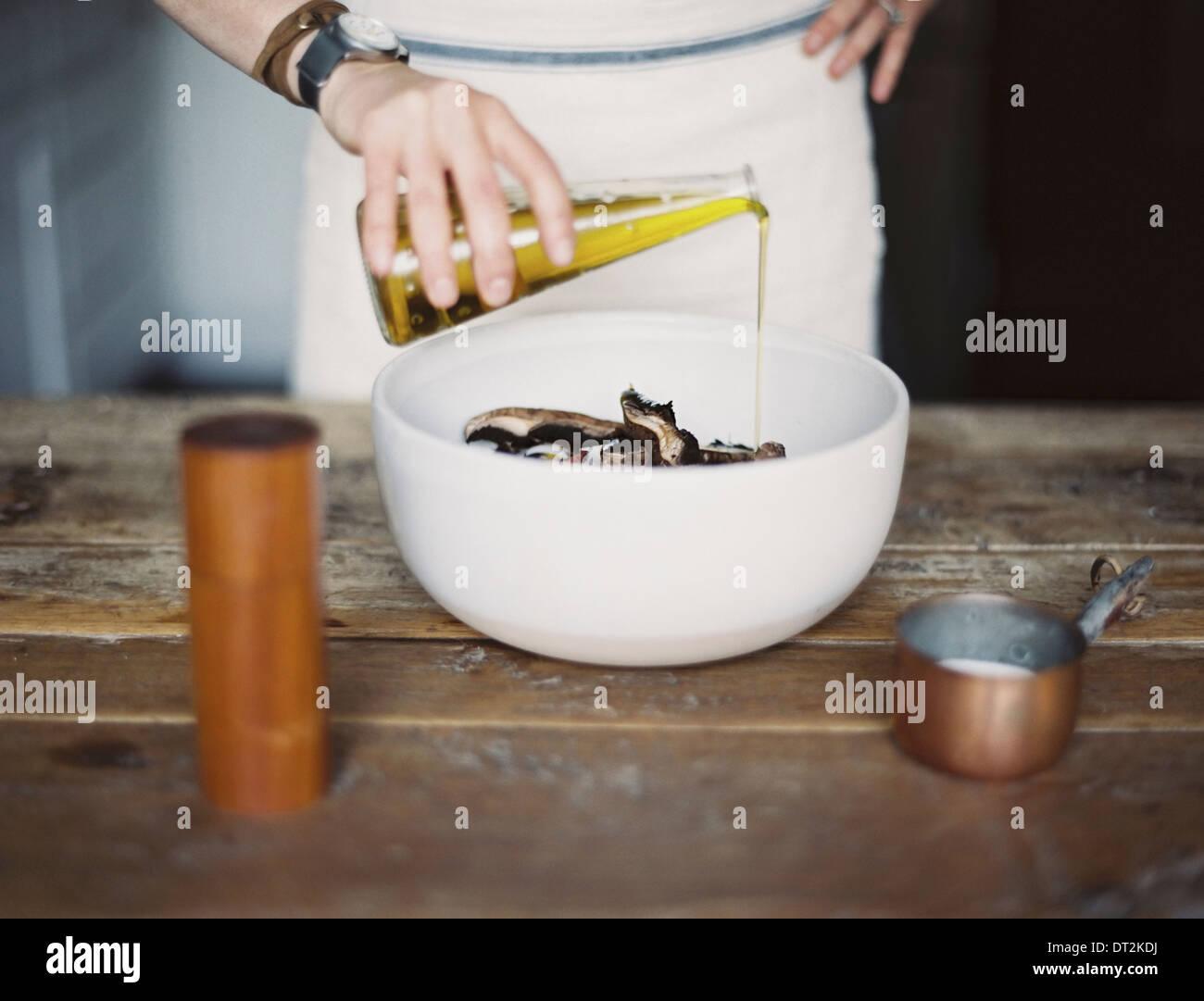 Una cucina domestica di una donna che indossa un grembiule medicazione una fresca insalata di verdure in una ciotola con olio Immagini Stock