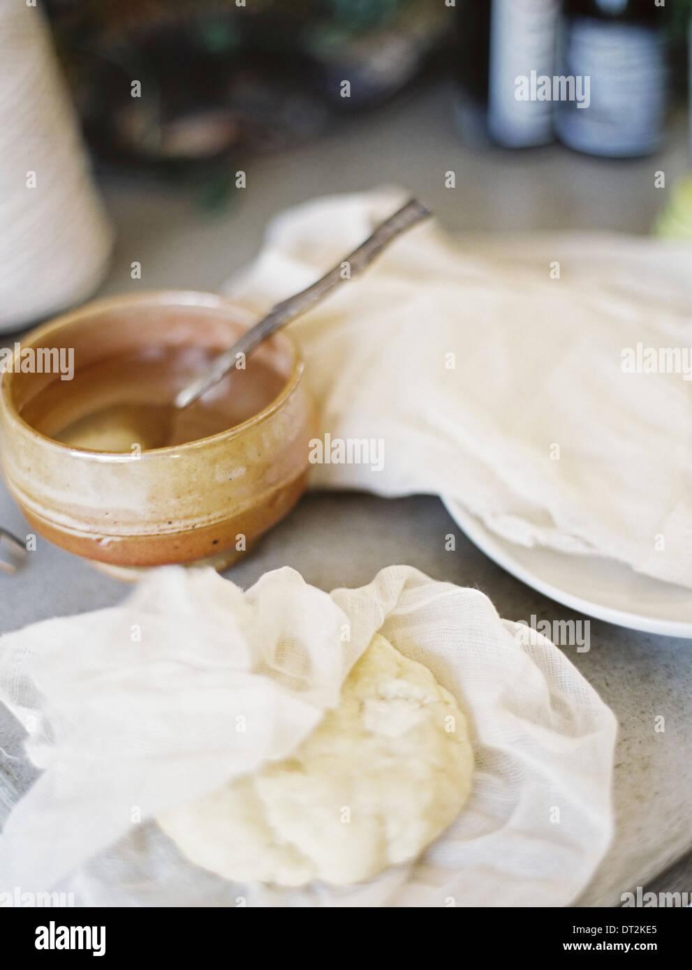 Un tavolo in una cucina domestica una ciotola di liquido con un cucchiaio in un blocco di pasticceria fresca parzialmente avvolti in una mussola square Immagini Stock