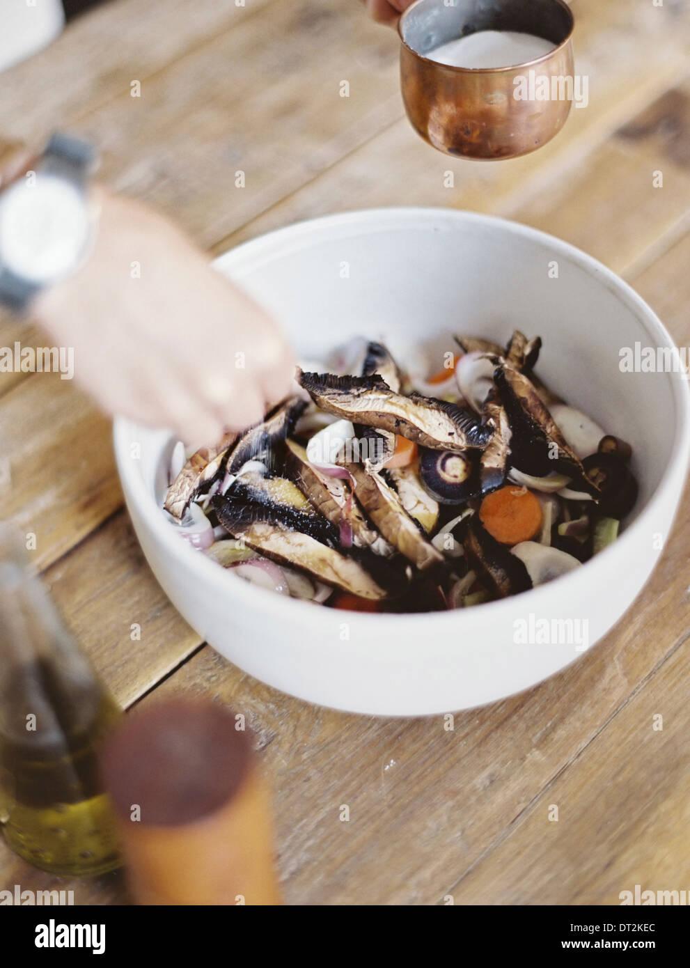 Una cucina domestica una ciotola di fresche verdure tritate in una ciotola bianca la mano di una persona di miscelazione Foto Stock