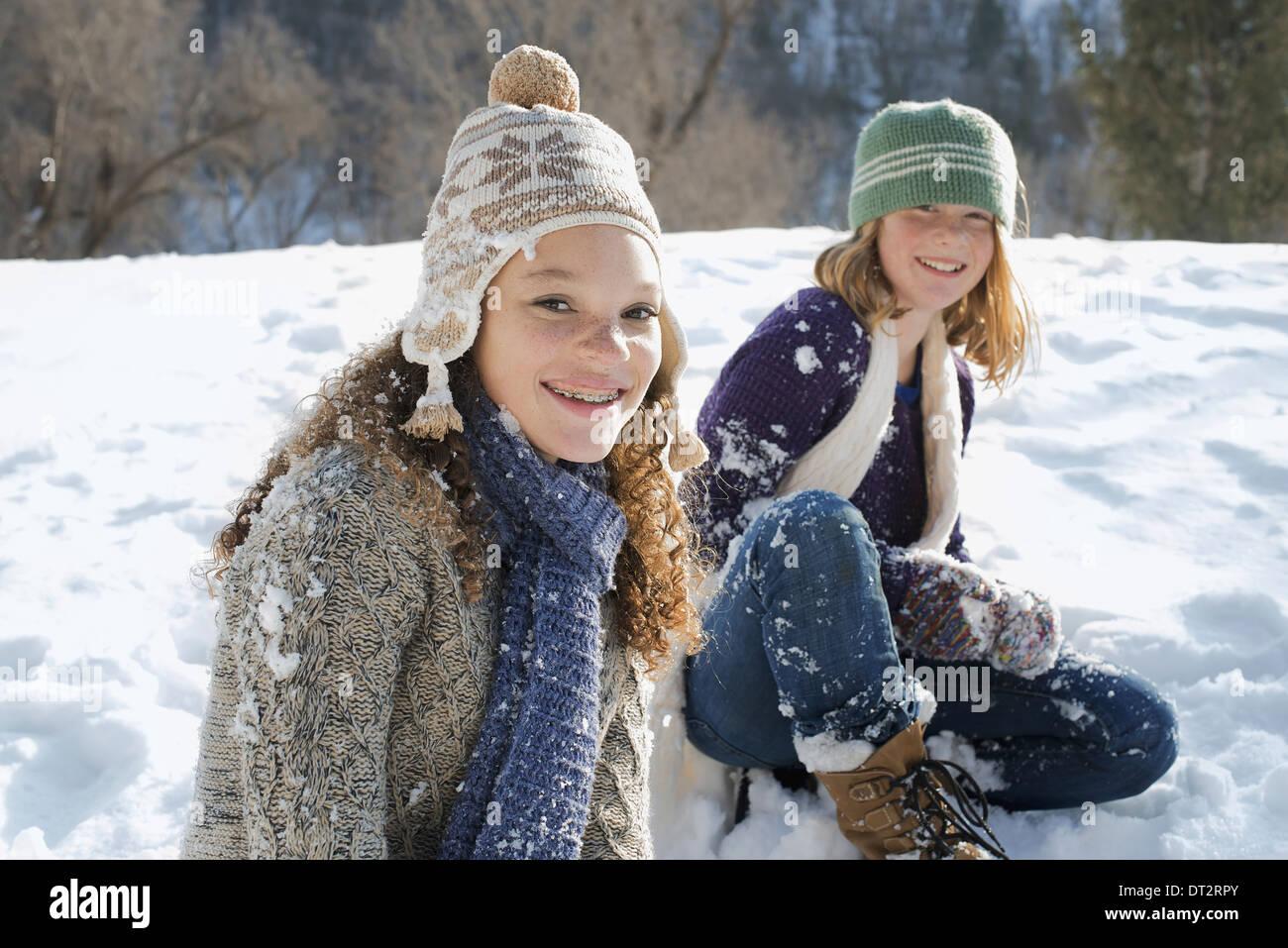 Paesaggio invernale con neve sulla terra una donna e un bambino seduto sul terreno di ridere Immagini Stock