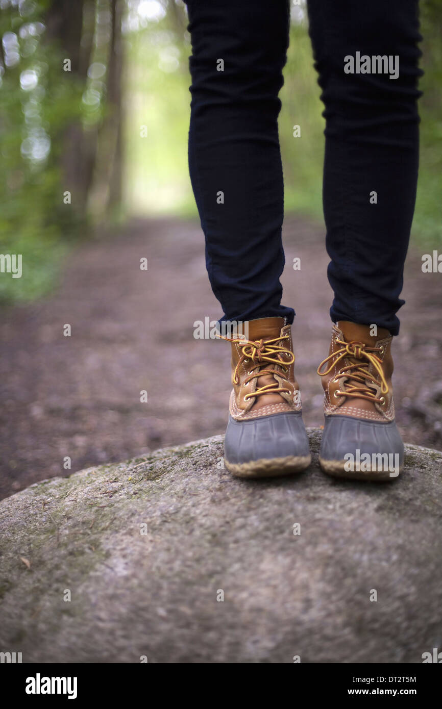 Una donna che indossa scarponi e jeans in piedi su una