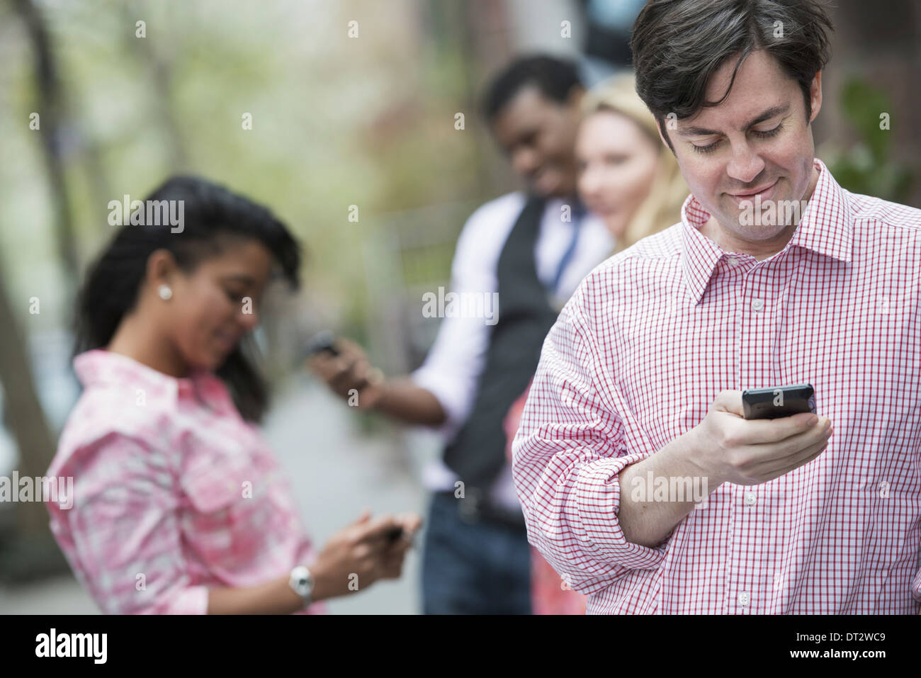 Vista su cityYoung persone all'esterno in un parco della città di tre persone che controllano che guarda i loro telefoni cellulari Immagini Stock