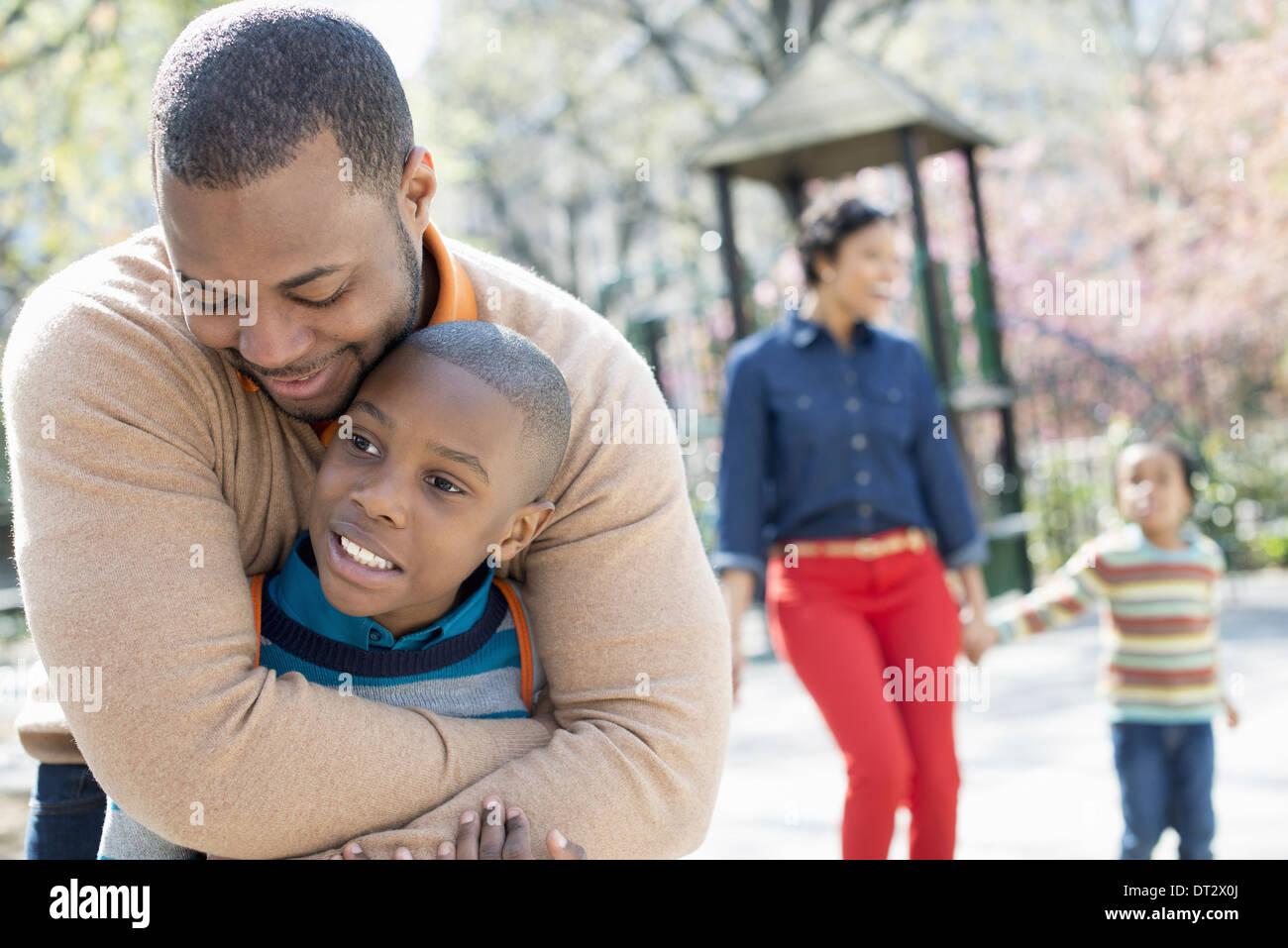 Una famiglia di genitori e due ragazzi di trascorrere del tempo insieme a padre abbraccia il suo figlio Immagini Stock